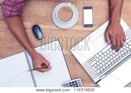 Cropped image of businessman writing on book while working on laptop in office