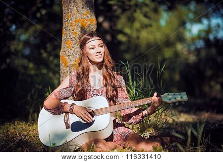 Beautiful Young Hippie Girl Sitting Under The Tree And Playing The Guitar
