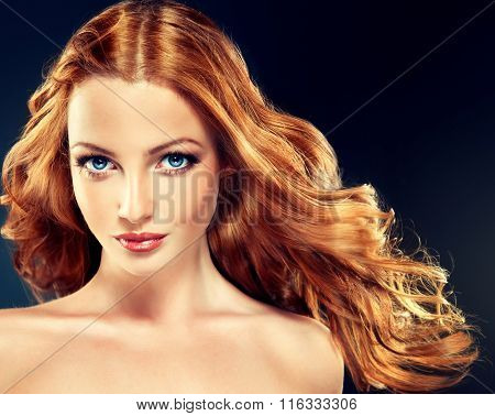 Beautiful model with long curly red hair .