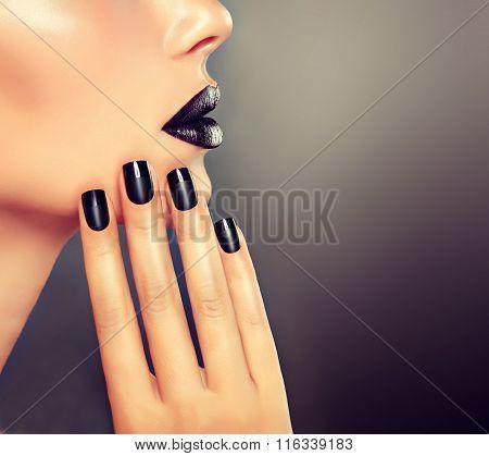 Beautiful girl showing black manicure nails .
