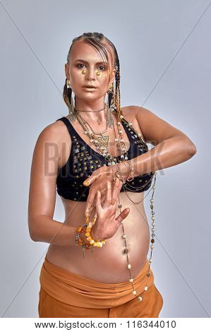 beautiful eight months pregnant woman, art make up, gold colors