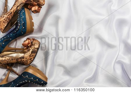 Denim And Leopard Shoes Lying On White Silk