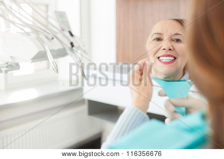 Cheerful mature lady is checking work of orthodontist