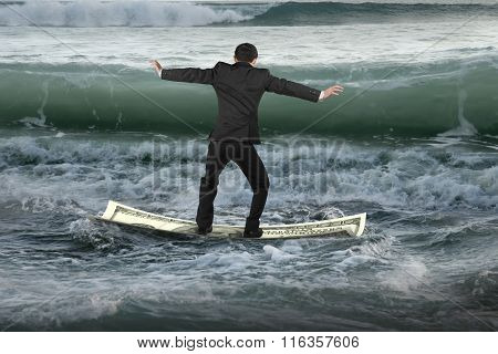 Businessman Balancing On Money Boat Floating In Ocean With Waves