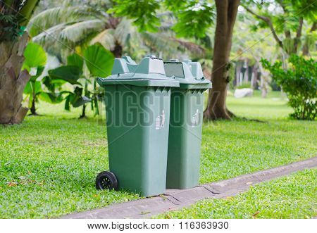 two green recycle bin in the park