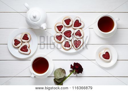 Heart shaped cookies for Valentines day with teapot, two cups of tea and rose composition