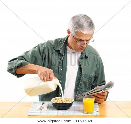 Middle Aged Man Pouring Milk Into His Cereal Bowl