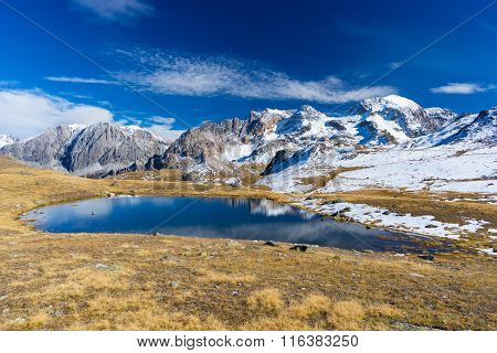 High altitude blue lake in idyllic uncontaminated environment once covered by glaciers. Reflection of majestic snowcapped mountain range on water surface. Wide angle shot in the Italian French Alps. poster