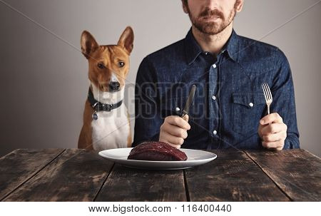 Man With His Dog Sit In Front Of Steak