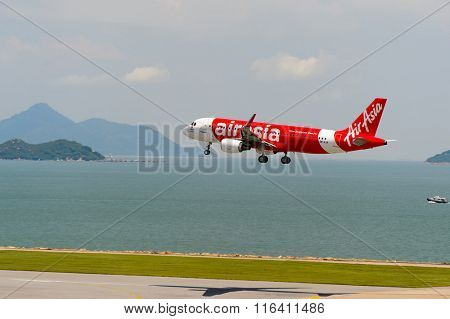 HONG KONG - JUNE 04, 2015: Air Asia aircraft landing at Hong Kong airport. AirAsia Berhad is a Malaysian low-cost airline headquartered near Kuala Lumpur, Malaysia.