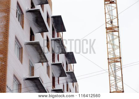 Tall crane and balconies of building under construction on blue sky at sunny snowy winter day