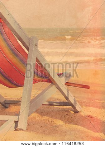 Deckchair on the beach in the sand at sunset - travel and summer holiday concept in retro style