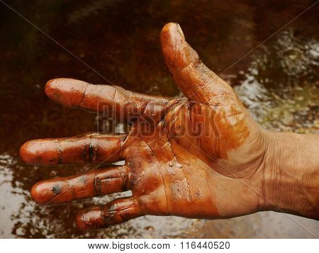 An Indonesian oil worker works with bare hands at a highly polluted oil field in Java, Indonesia