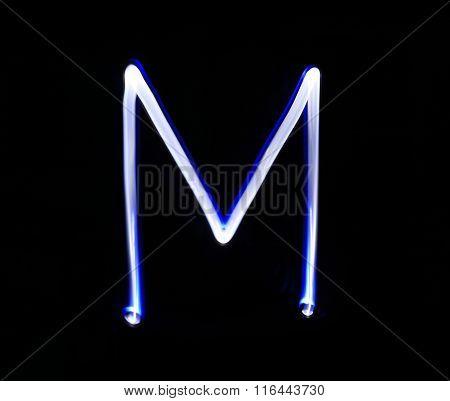 M Mike Alphabet Hand Writing Blue Light  Over Black Background.