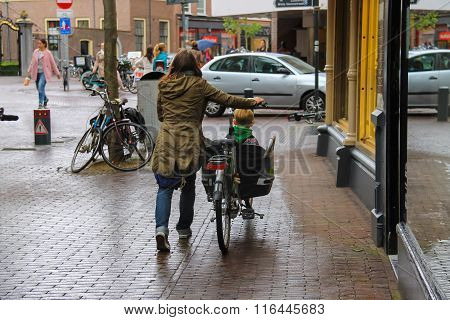 A Woman Carries A Child By Bicycle In The  Historic Center Of Haarlem, The Netherlands
