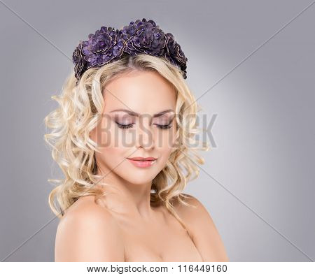 Gorgeous blond wearing purple flower alike crown with an enigmatic smile over grey background.