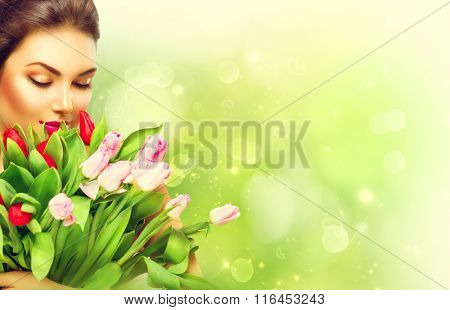 Beauty model Woman with Spring Flower bunch. Beautiful girl with a Bouquet of colorful Tulip flowers. Happy surprised model woman smelling flowers. Mother's Day gift. Valentine's Day. Springtime