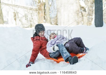 Sibling children laughing and riding downhill on winter orange toboggan sledge made of plastic outdo