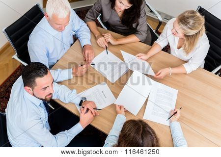 Lawyers having team meeting in law firm reading documents and negotiating agreements poster