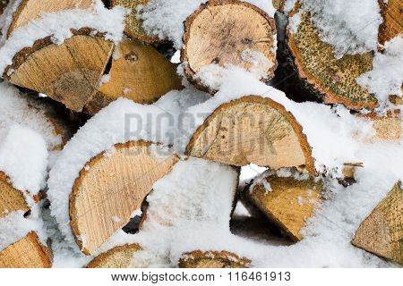 Winter background  texture pattern of stacked dry chopped firewood logs covered with snow