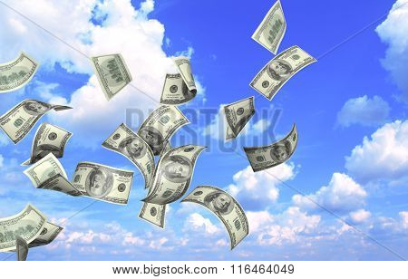 Flying banknotes of dollars on blue sky background