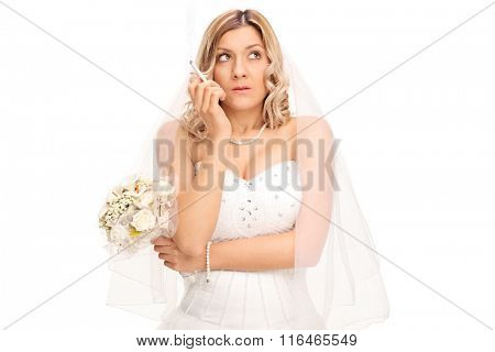 Young nervous bride in a white wedding dress holding a bouquet and smoking a cigarette isolated on white background