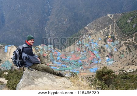 young trekker sitting above Namche Bazaar town on his way to Everest Base camp