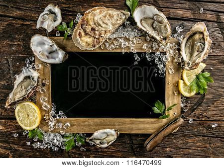 Oysters served on wood with blackboard