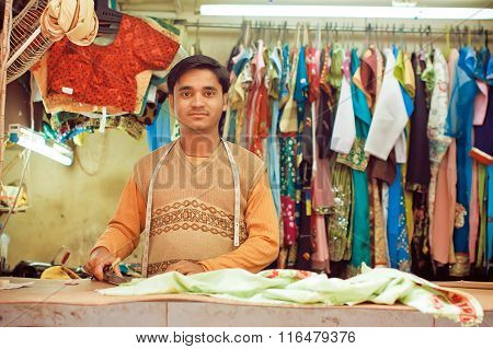 Young Tailor Sews Clothes In A Workshop For Making Dresses