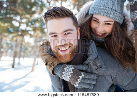 Smling beautiful couple walking in winter park and looking at camera