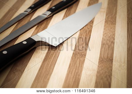 chef's knife and two other smaller knives on a cutting board with copyspace