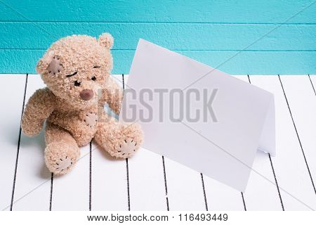 Teddy bear sitting on white wooden floor in blue-green background with blank note