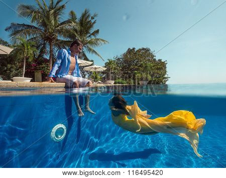 Man sit nearly swimming pool and Woman swimming underwater in the swimming pool