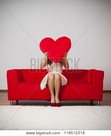 Woman holding a red heart in front of her face