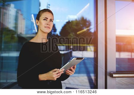 Female entrepreneur holding portable touch pad and looking away during work break