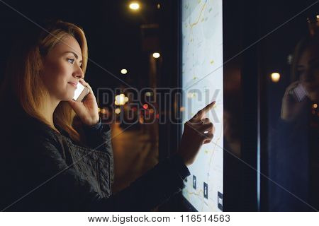 Pretty woman tourist talking on mobile phone while looks at map of the city on electronic bulletin