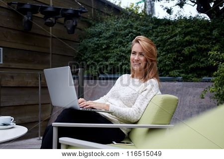 Pretty young woman smiling to someone during work on portable net-book in comfortable sidewalk cafe