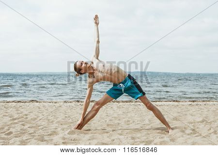Adult thin man with naked torso doing yoga on the beach. Utthita trikonasana pose poster