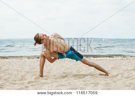 Adult thin man with naked torso doing yoga on the beach. Parivritta parshvakonasana pose