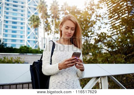 Pretty woman reading text message on her cell telephone while standing on the street