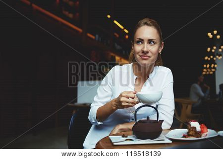 Dreaming woman holding cup of green tea while sitting at the table of coffee shop with sweet dessert