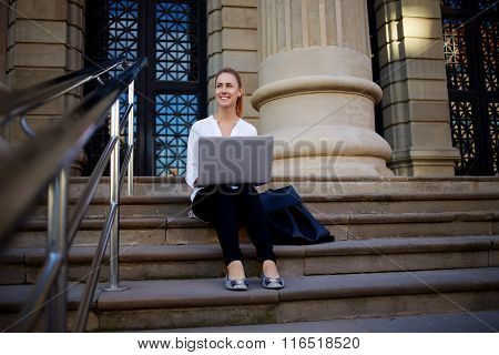 Smiling female student using portable net-book while sitting near institution or University