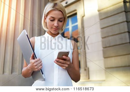 College student with laptop computer chatting on mobile phone while waiting for classmate
