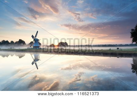 Beautiful Sunrise Over Dutch Windmill By River
