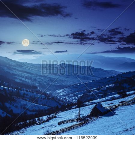 Woodshed On The Hillside In Winter Mountains At Night