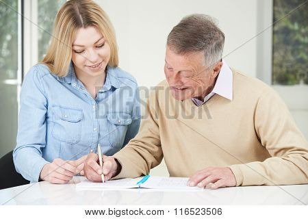 Senior Man Playing Completing Sudoku Number Puzzle With Teenage Daughter