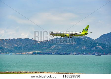 HONG KONG - JUNE 04, 2015: Jin Air aircraft landing at Hong Kong airport. Jin Air Co. Ltd is a low cost airline originating from South Korea, and a wholly owned subsidiary of Korean Air.