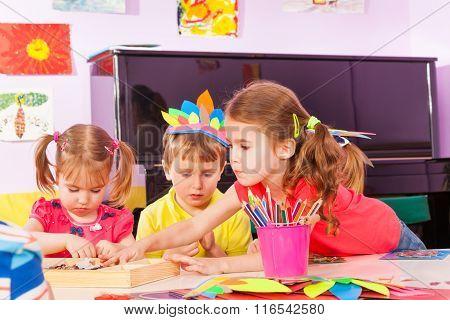 Girl stretching for paper in kindergarten class