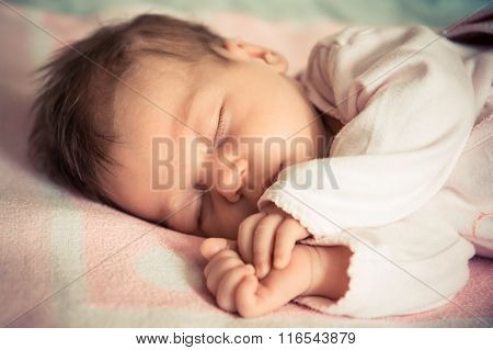 Newborn baby girl sleeping on soft blanket with natural light
