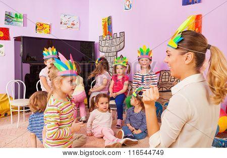 Children play with teacher wear Indian headwear